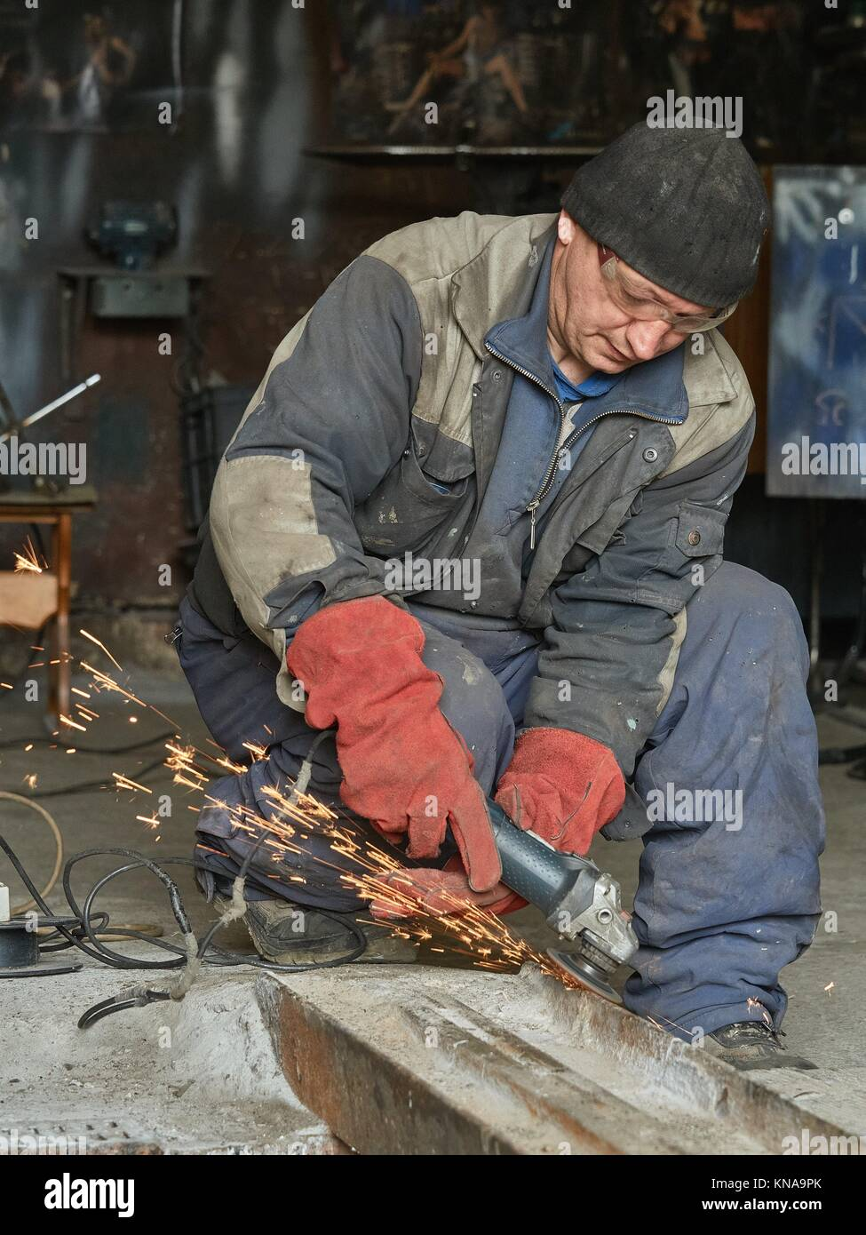 Worker grinds a metal rail for subsequent welding. The photo shows the sparks from the grinding wheel. - Stock Image