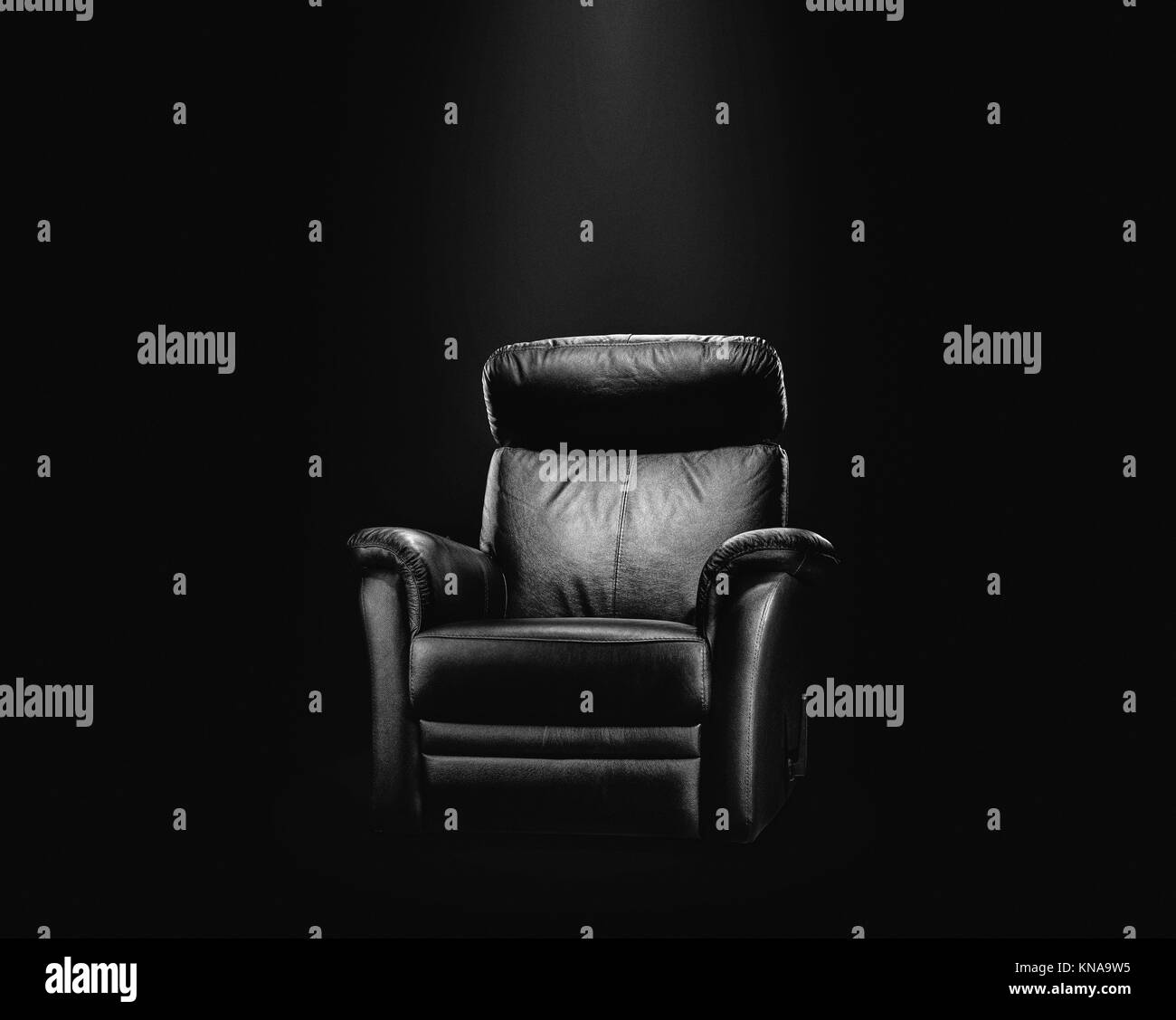 Black leather armchair in spotlight, dark background. - Stock Image