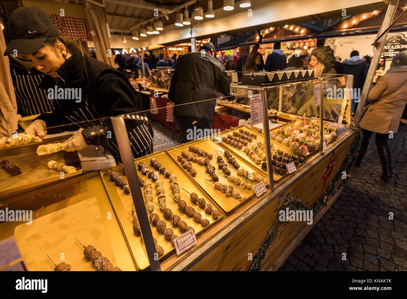 Market stall traders serve food and drink to customers at Manchester Christmas Markets Around The City, Manchester, Stock Photo