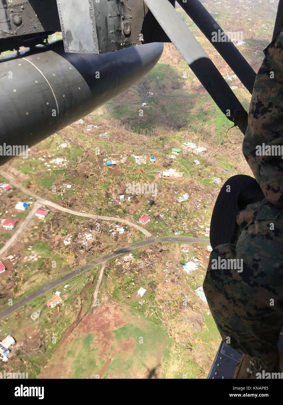 U.S. service members fly over the Caribbean island of Dominica, Oct. 9, 2017. The island was devastated by Hurricane - Stock Image