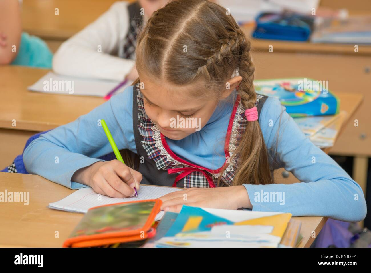 First-grader at a lesson of mathematics to solve the examples notebook. - Stock Image