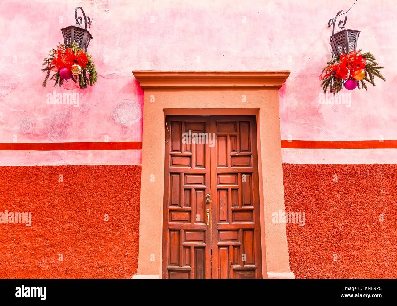 Pink Red Wall Brown Door Christmas Decorations San Miguel de Allende Mexico. - Stock Image