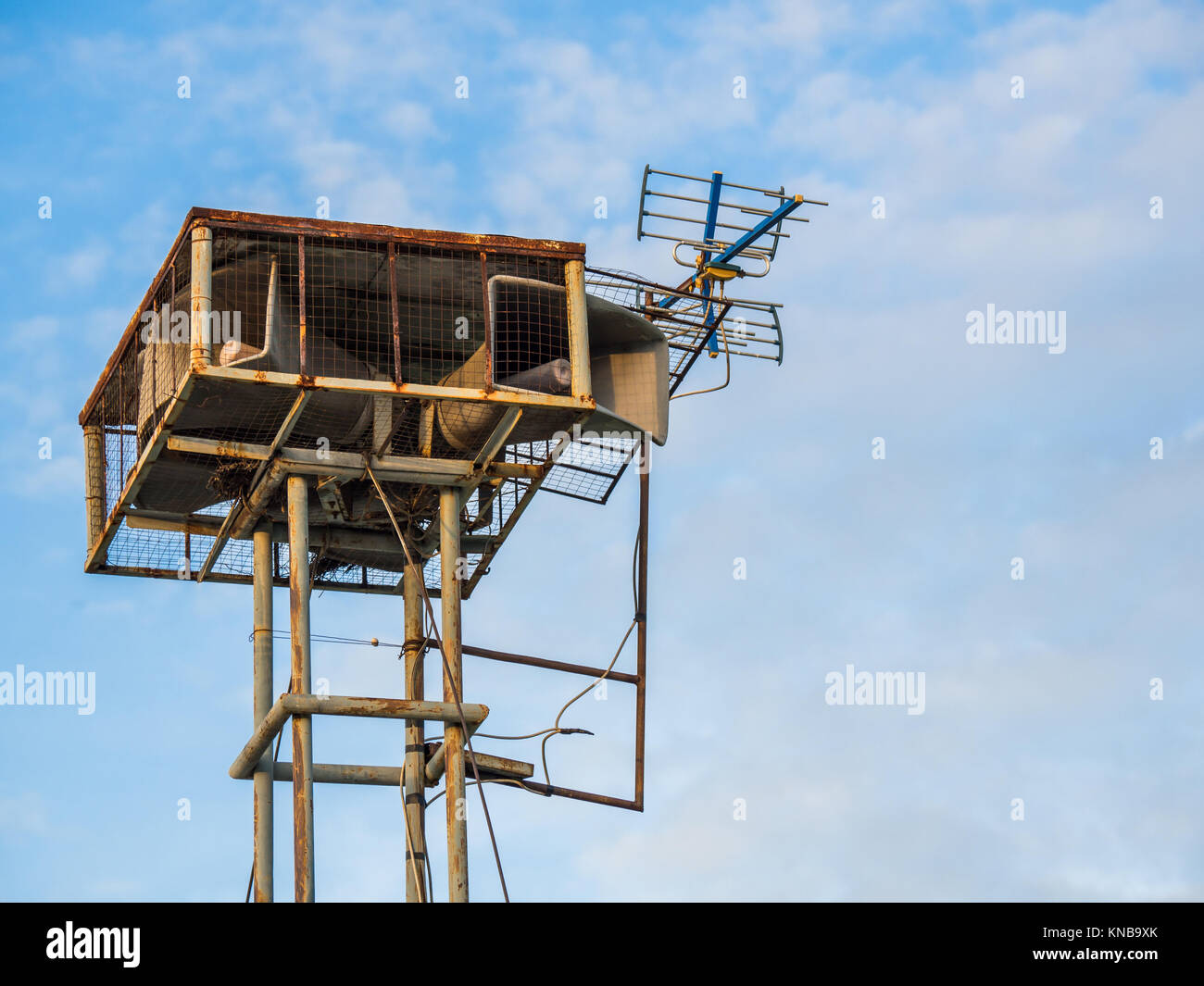 Old public loudspeakers broadcast vintage style on high tower the blue sky background - Stock Image