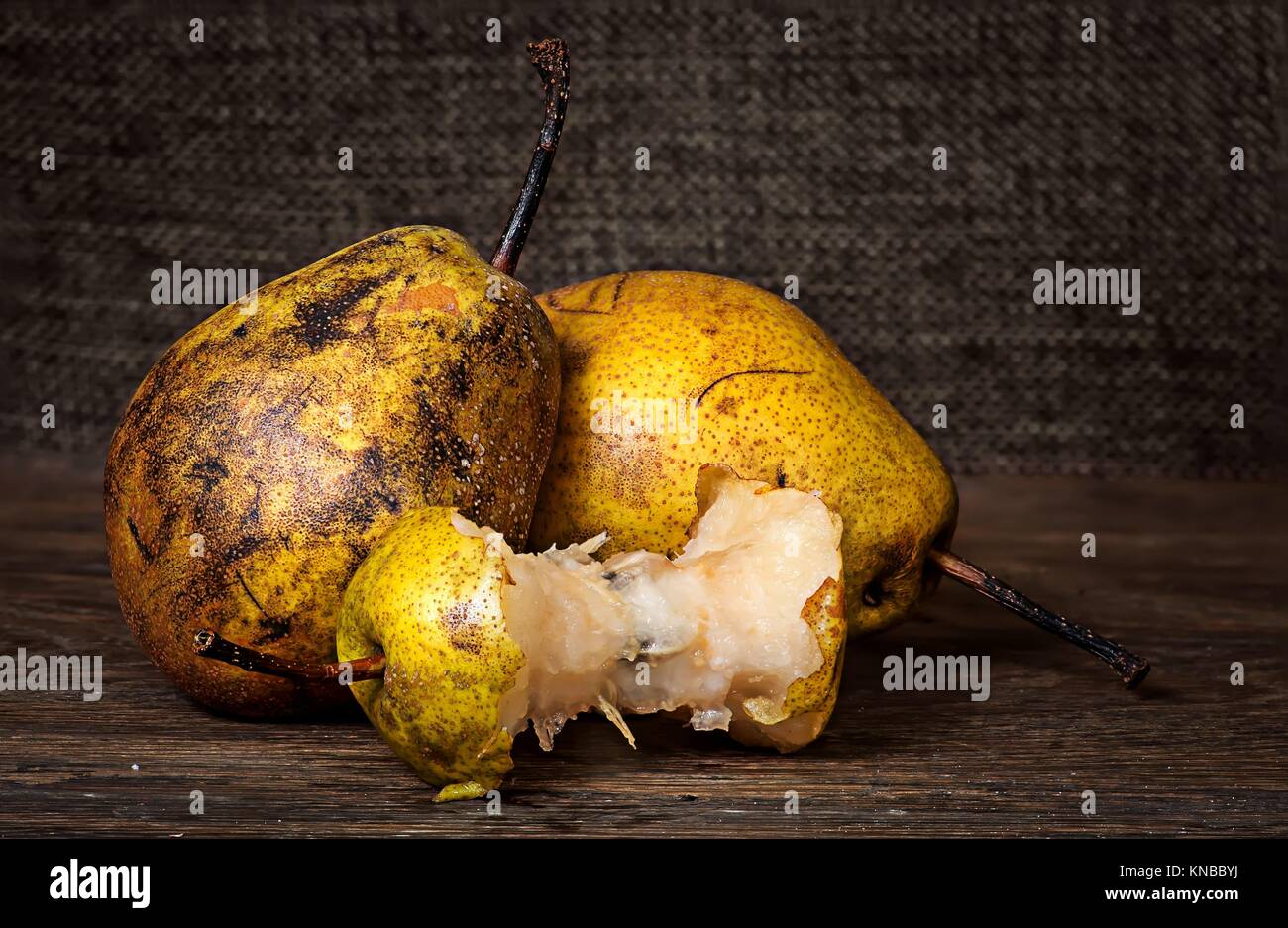 Two pears and stub on wooden table background sacking. - Stock Image