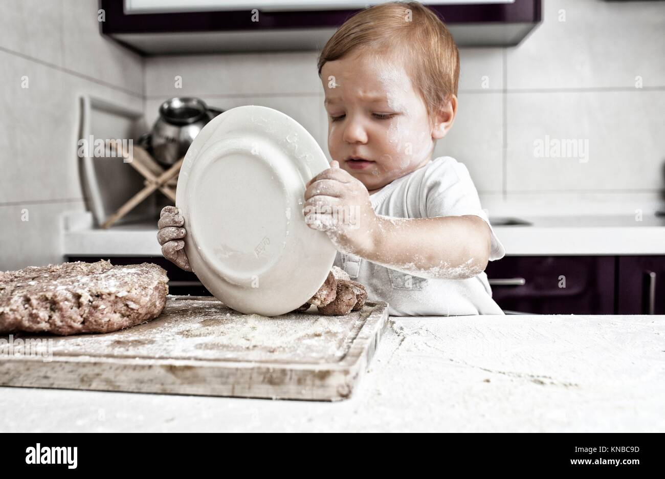 Baby boy preparing meatballs. He is dumping the plate. - Stock Image