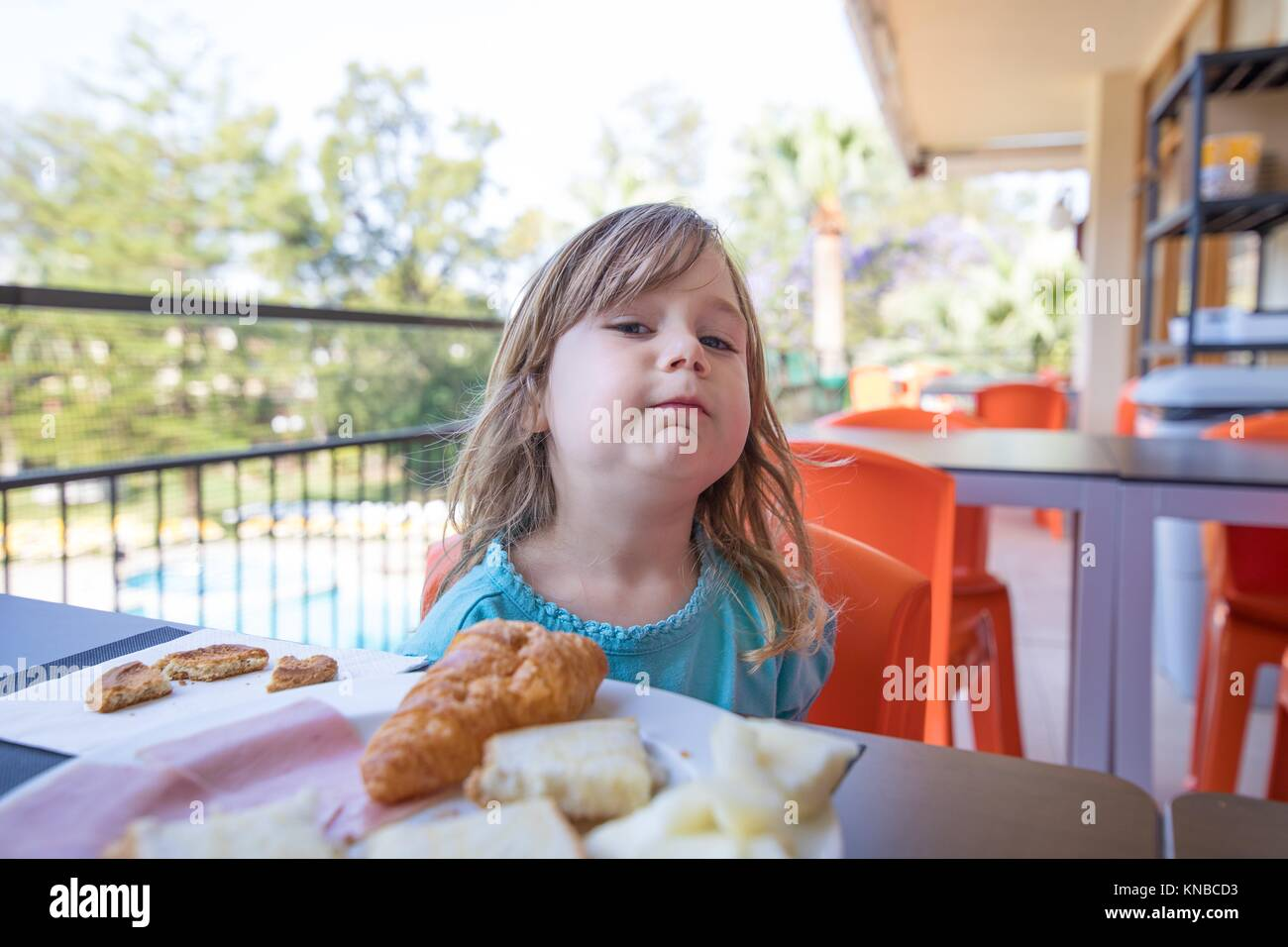 portrait of blonde caucasian child three years old with blue shirt, at breakfast, looking with challenging funny - Stock Image