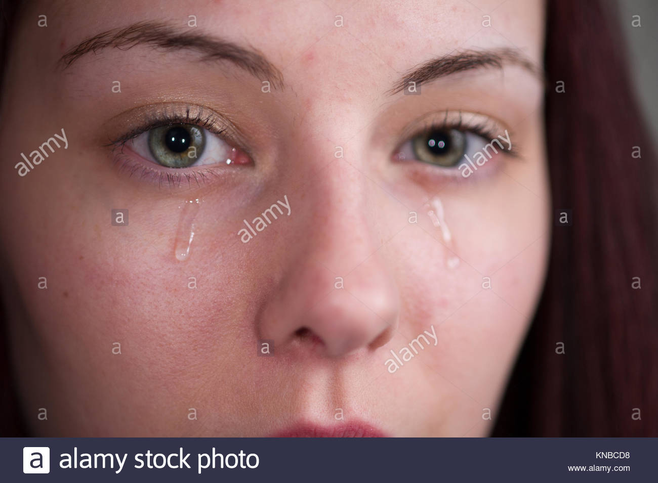 close up of a woman's face with tears running down her cheeks - Stock Image