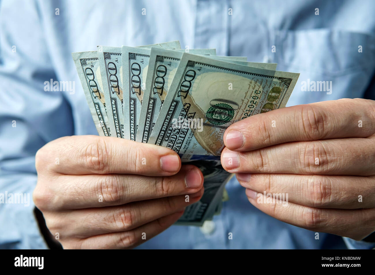 man counting five hundred US dollars. The businessman thinks of profit. Dollar bills in the hands of men on the - Stock Image