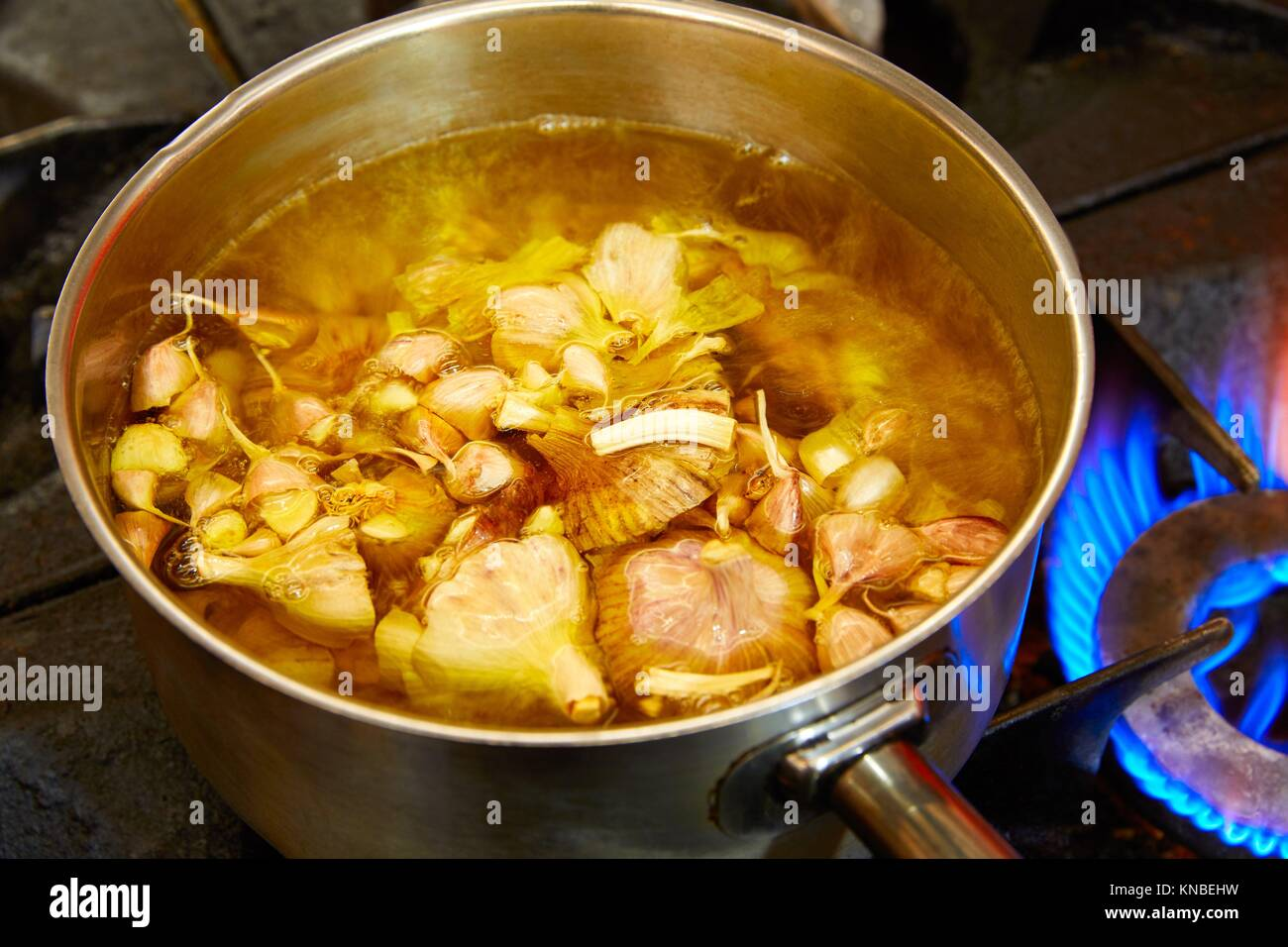 Cooking food fire place stock photos cooking food fire place stock garlic boiling soup in a pan at kitchen fire stock image forumfinder Choice Image