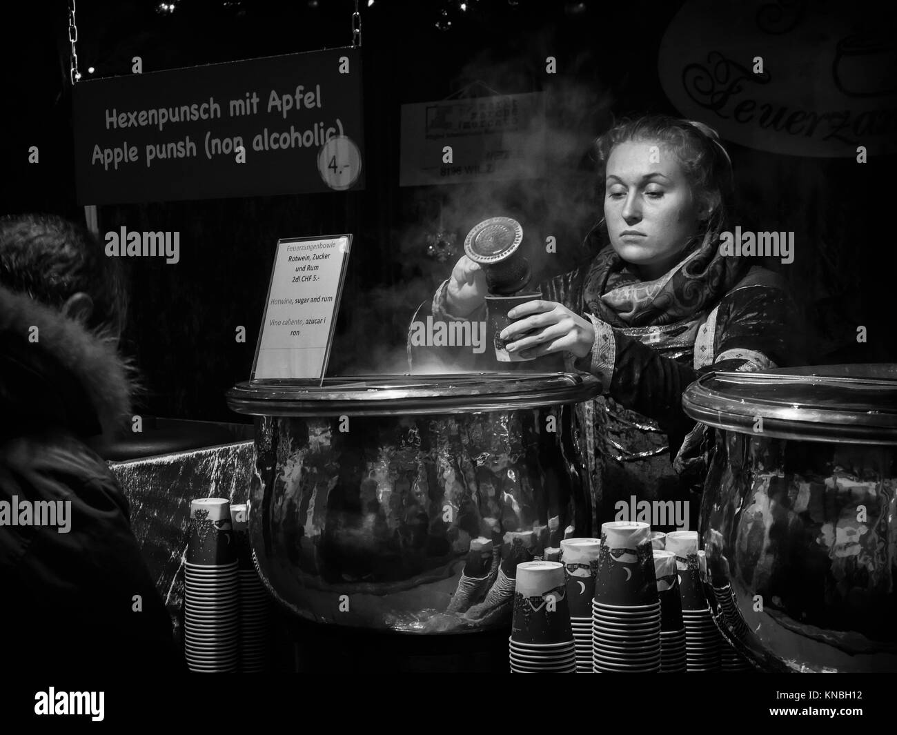 Serving punch at christmas market in Zurich, Switzerland. - Stock Image