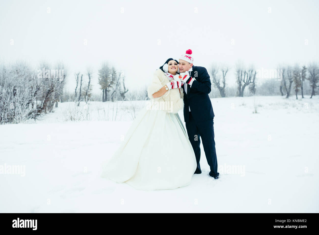 The full-length shot of the charming happy newlyweds in funny hats and gloves holding cups and standing close to - Stock Image