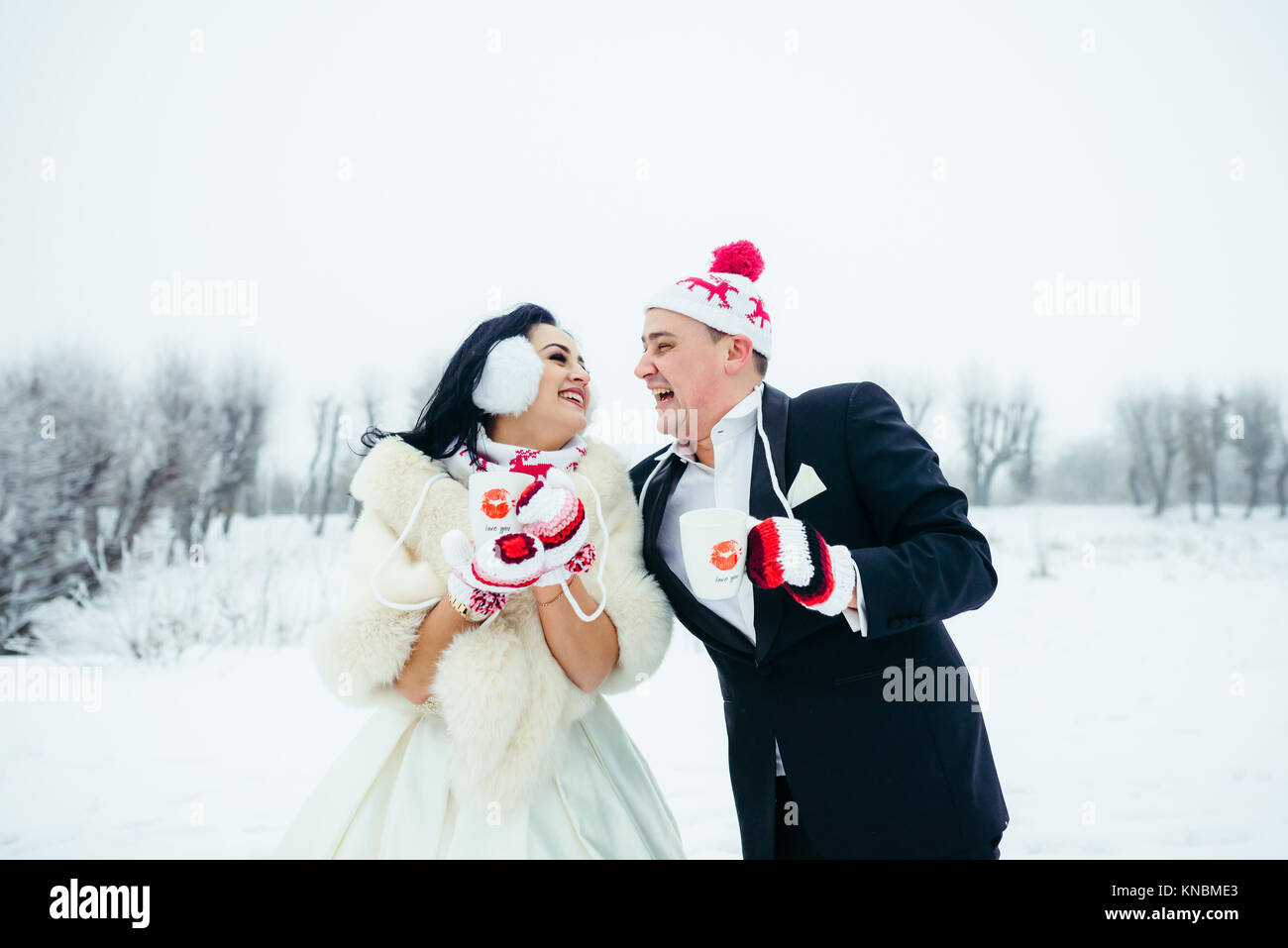 Laughing newlyweds couple in the funny hats and gloves holding the cups with coffee while spending time on the snowy - Stock Image