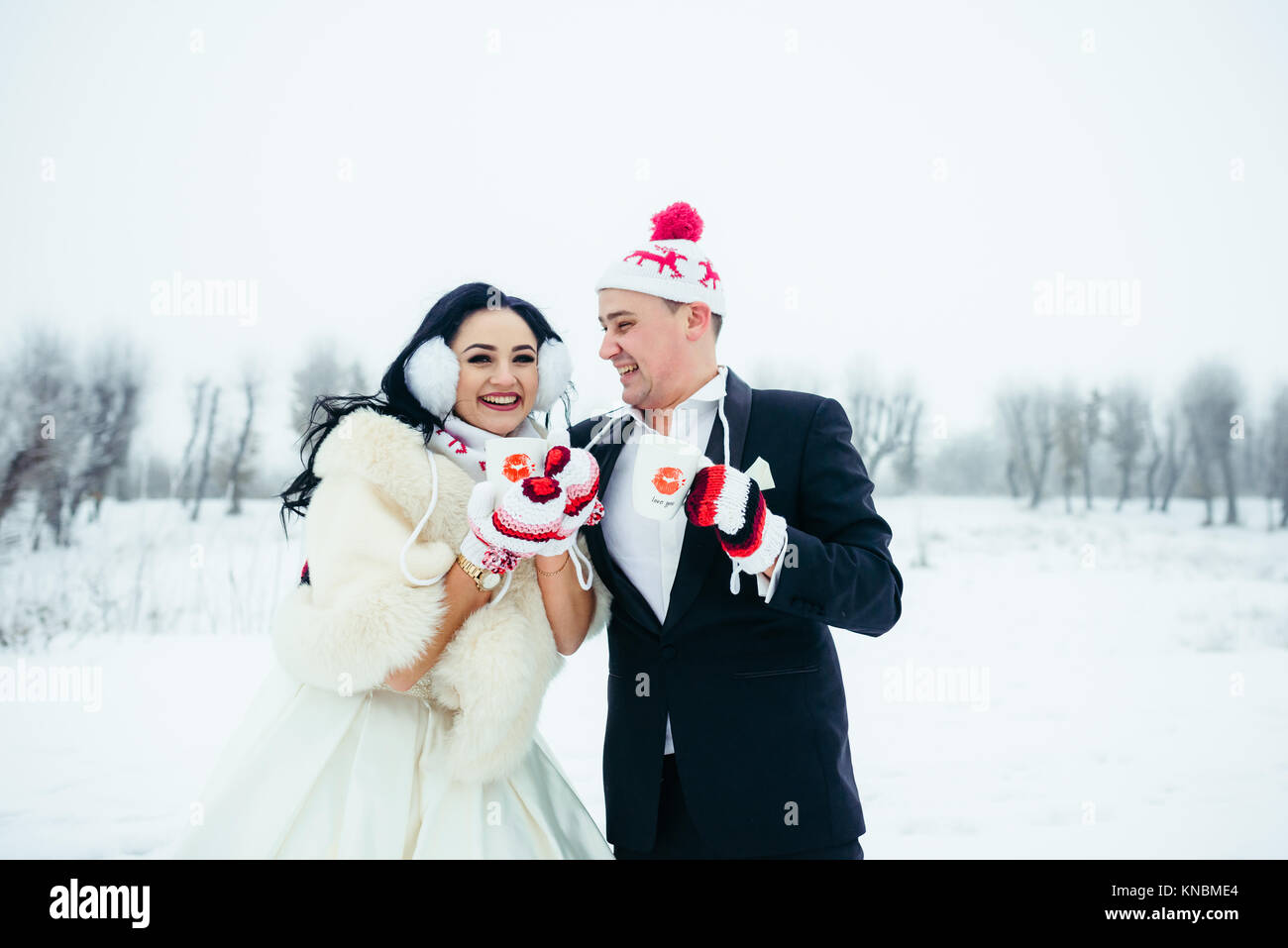 Close Up Portrait Newlyweds Couple Funny Hats Holding Cups Cofee Tea Winter Snowy Wedding Happy Gloves Fun. - Stock Image