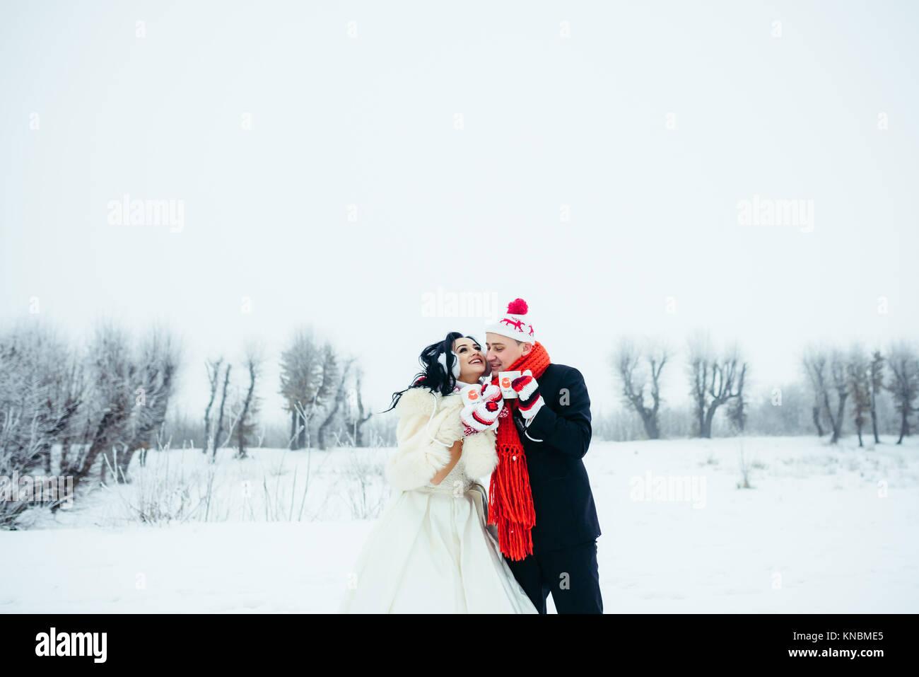 Portrait Happy Joyful Newlyweds Couple Love Wearing Funny Hats Gloves Close-up Cups Coffee Tea Wedding Winter Snowy - Stock Image