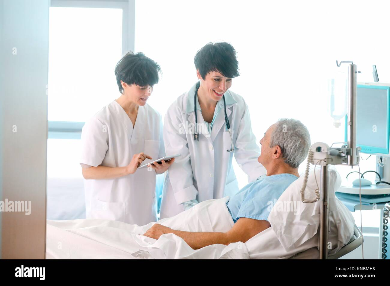 Patient in hospital room attended by a doctor, Hospital Stock Photo