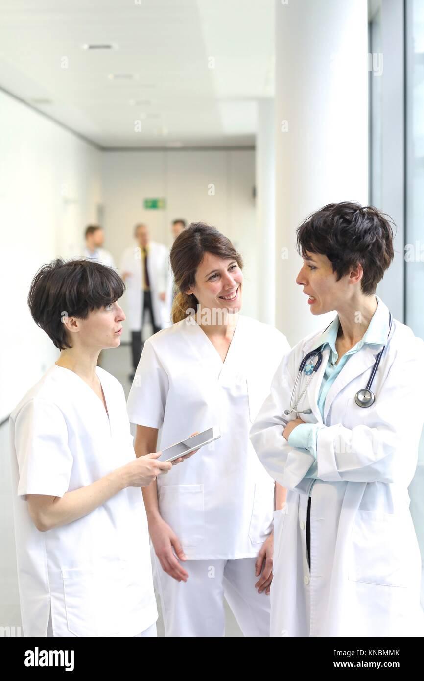Doctors and nurses talking in corridor, Hospital - Stock Image