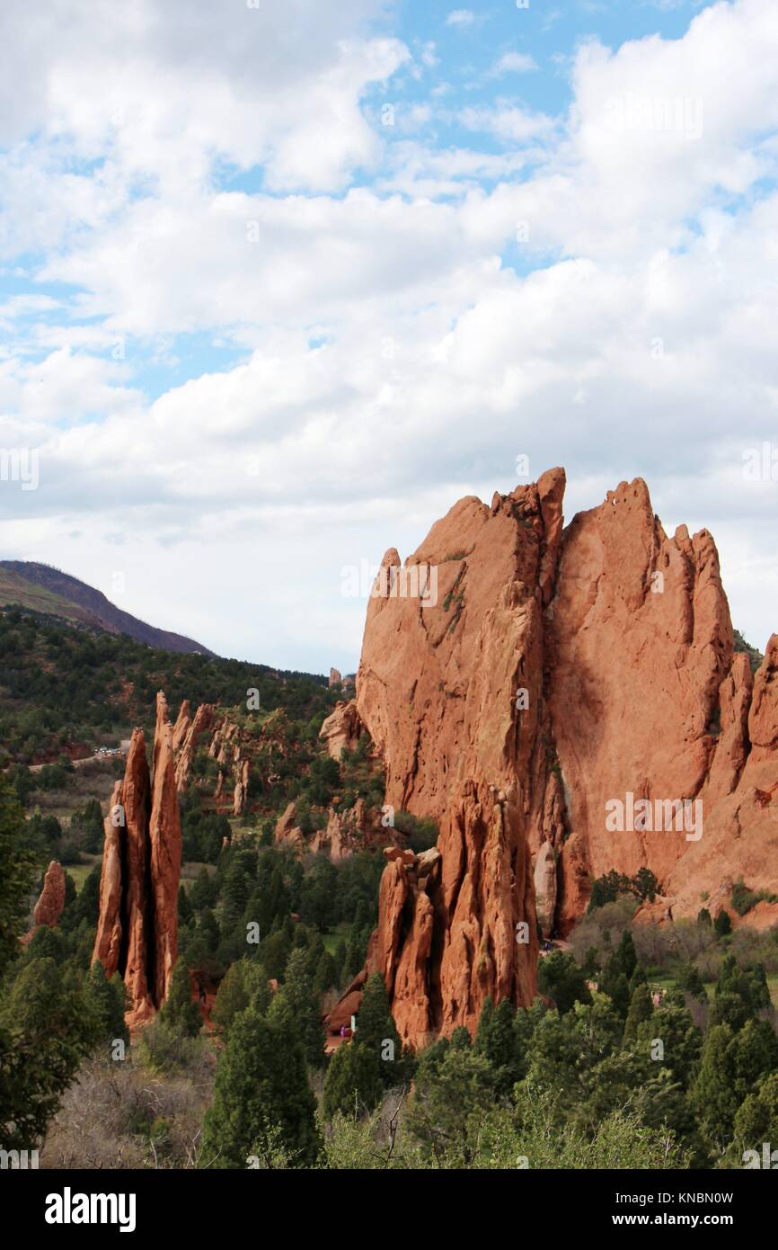 Sweeping landscape view of red rock pinnacles and unique rock formations with pine covered mountains in the background - Stock Image