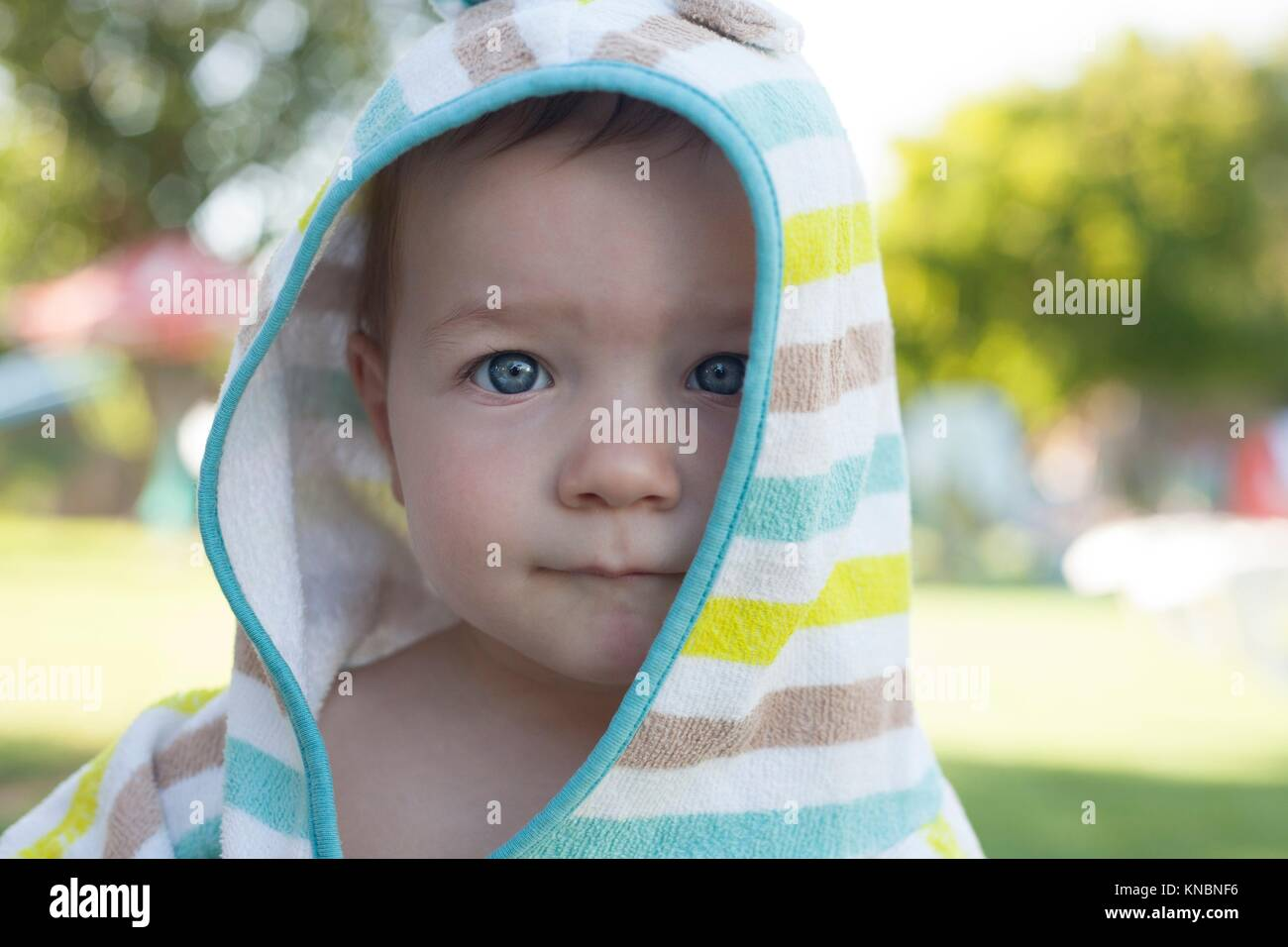 1 year baby boy with hooded poncho towel after swimming. Portrait. - Stock Image