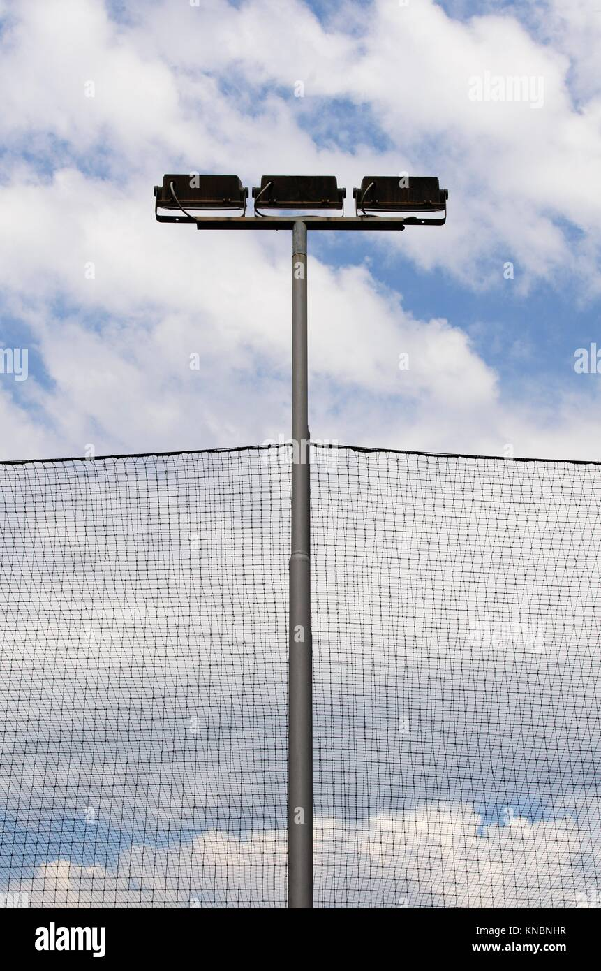 Lighting lanterns and protection grids in front of the blue sky with white clouds. - Stock Image