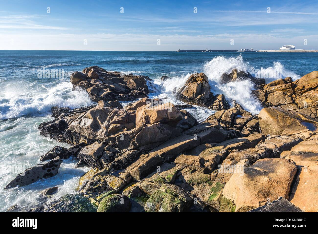Rocks on the beach in Nevogilde civil parish of Porto, Portugal. Port of Leixoes Cruise Terminal building on background. Stock Photo