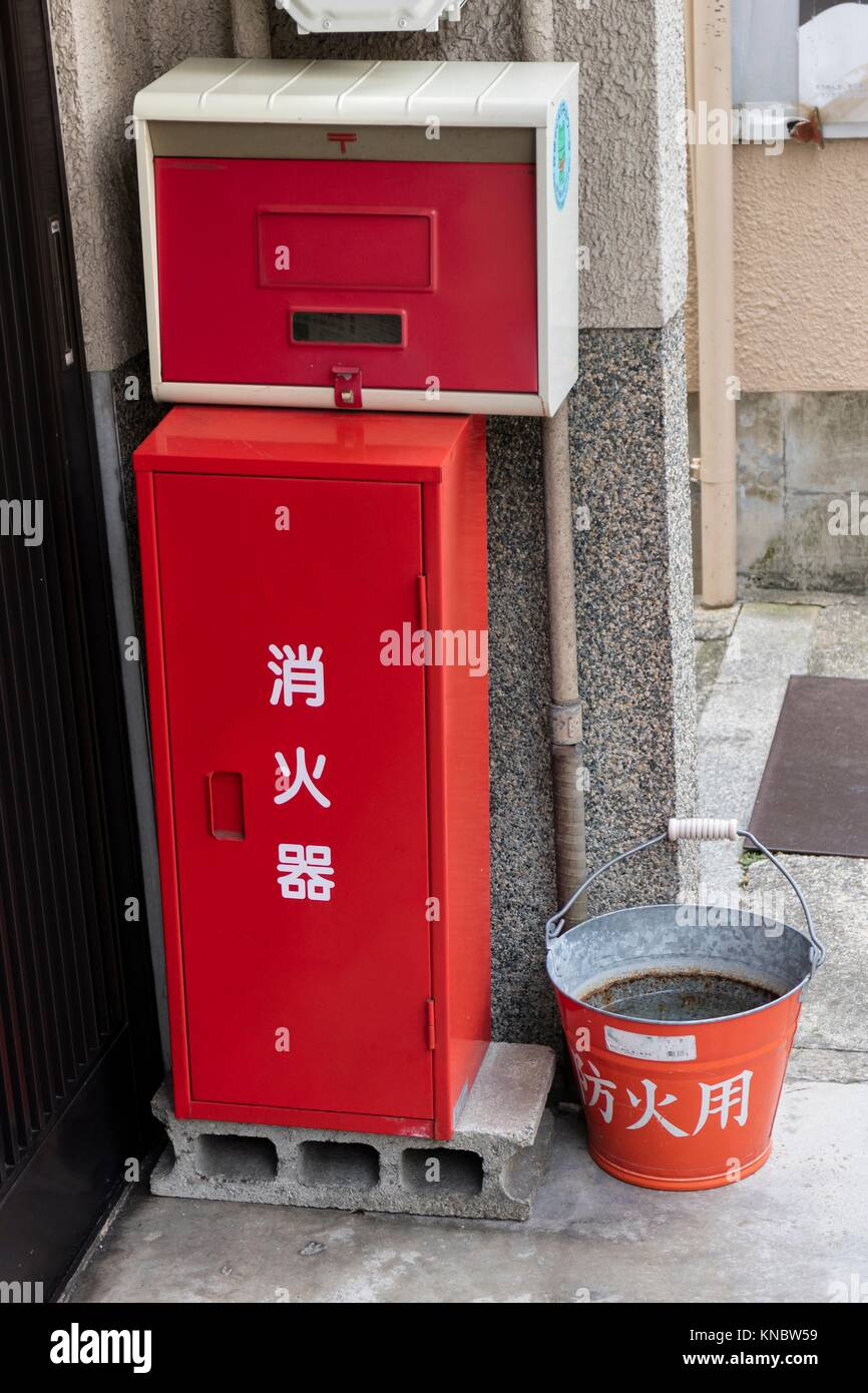 Kyoto, Japan, Traditional red fire bucket with water in front of the house as fire prevention in Kyoto. Stock Photo
