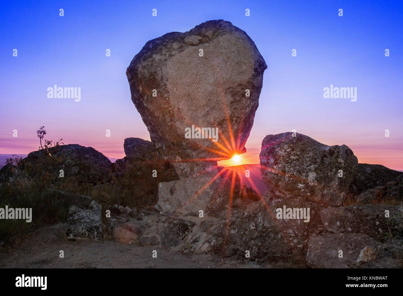 Sun rising between megalithic monument of Cancho Que Se Menea. In English shifting rock. Montanchez, Spain. - Stock Image