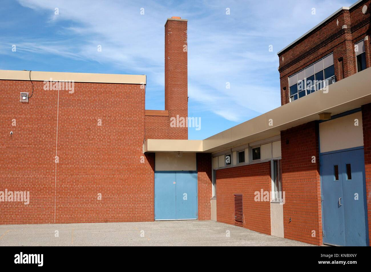 Playground area, smokestack and doors of an inner city Catholic elementary public school after school is out in - Stock Image