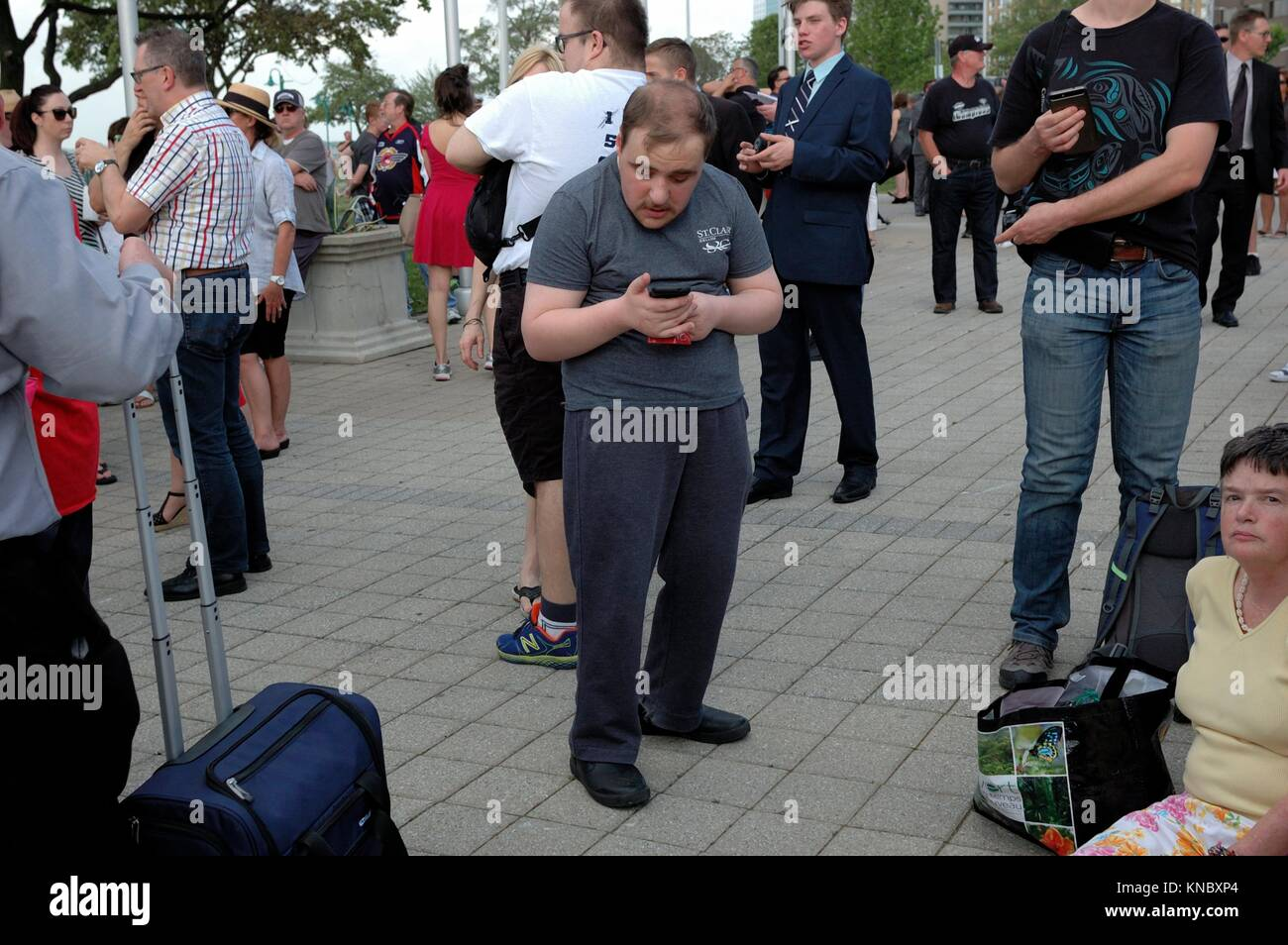 A man bends over to look at his smartphone while a crowd of people wait for the start of a ceremony involving hockey - Stock Image