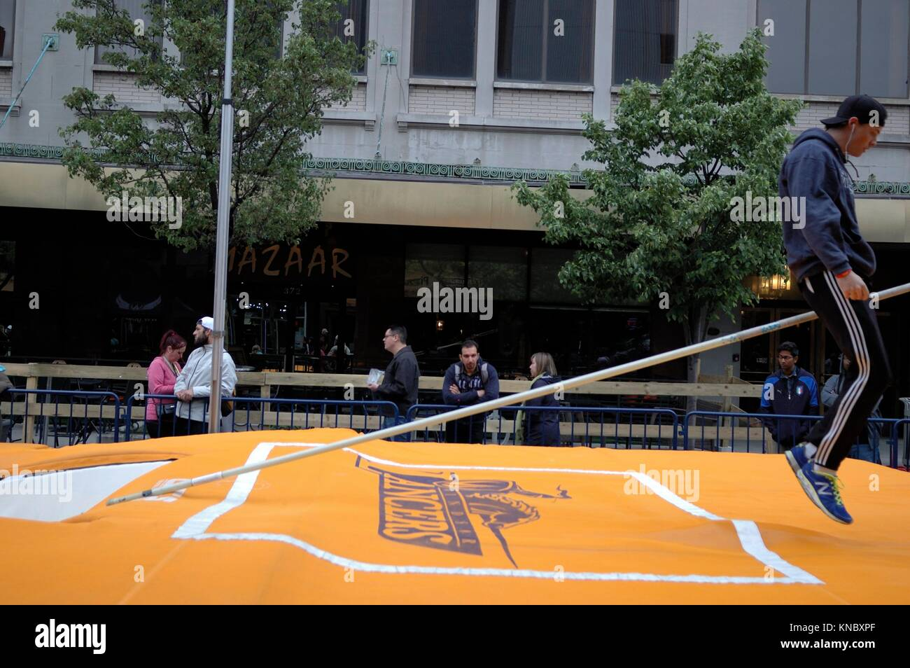 A male pole vault university athlete straddles a pole after his warm up attempt during a downtown exhibition sponsored - Stock Image