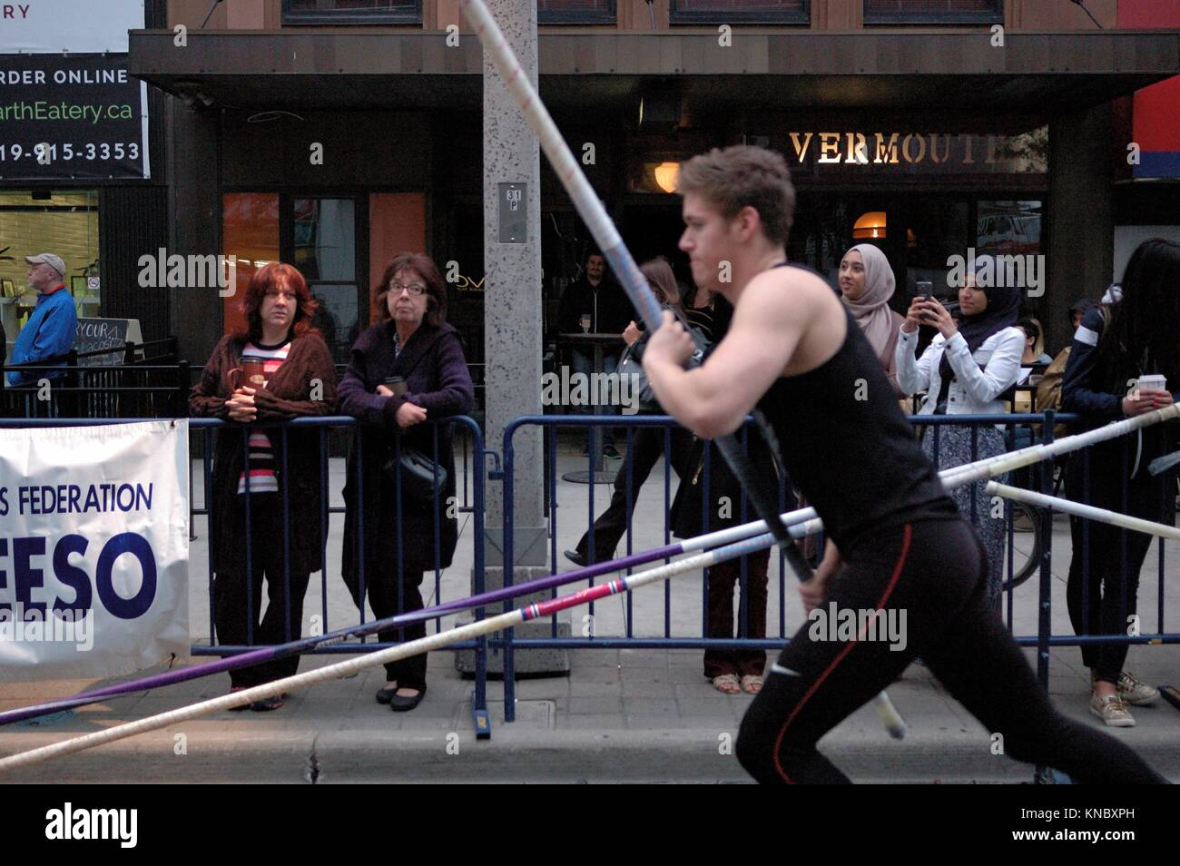 Two women watch as a male pole vaulter starts his jump attempt. The downtown event is sponsored by the local university. - Stock Image