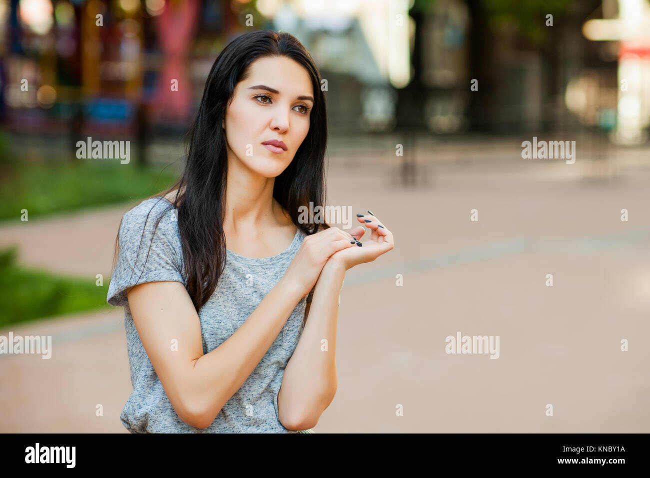 Young thoughtfull girl in gray shirt with long brunette hair in the street. Close up portrait - Stock Image