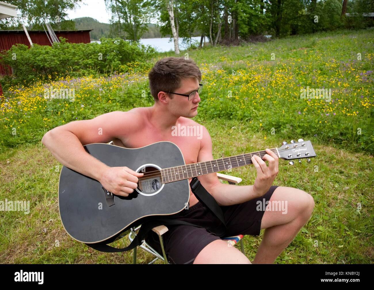 Man playing guitar outdoors, countryside of northern Sweden. - Stock Image