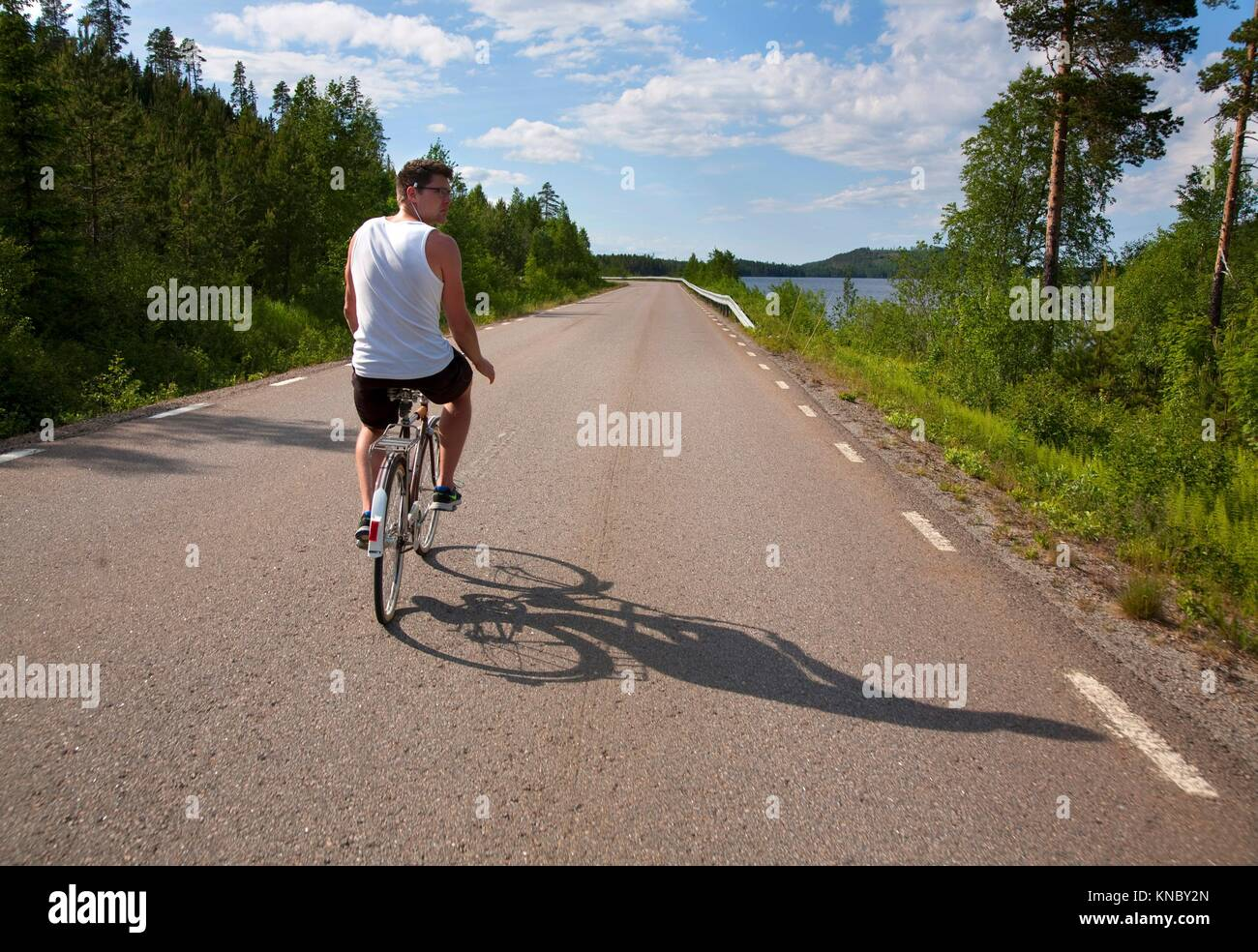 Man riding bicycle on the road, countryside of northern Sweden. - Stock Image