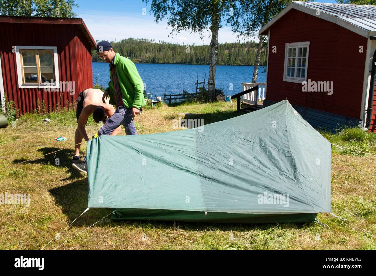 Brothers putting up a tent, Northern Sweden. - Stock Image