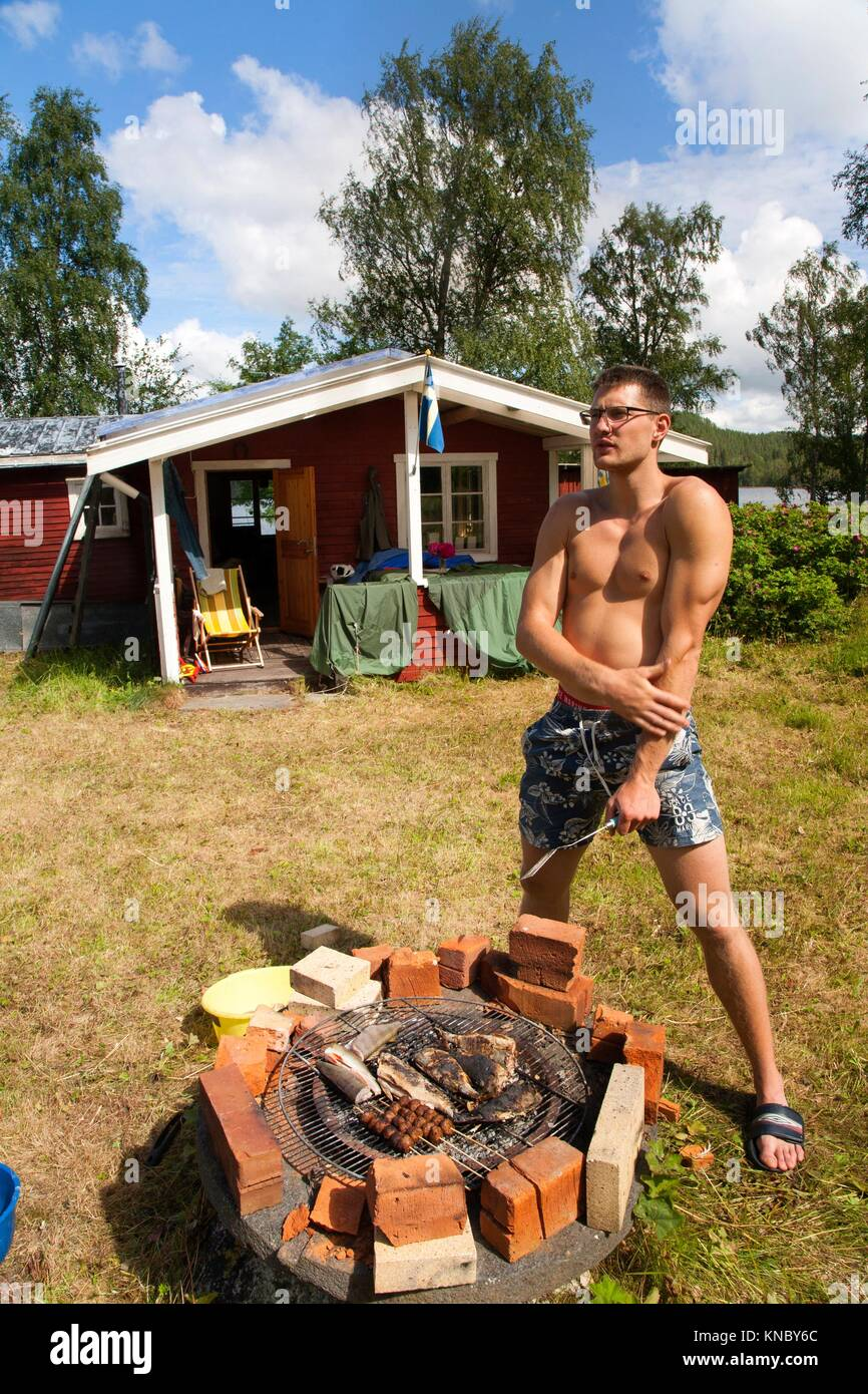 Man grilling fish, Northern Sweden. - Stock Image