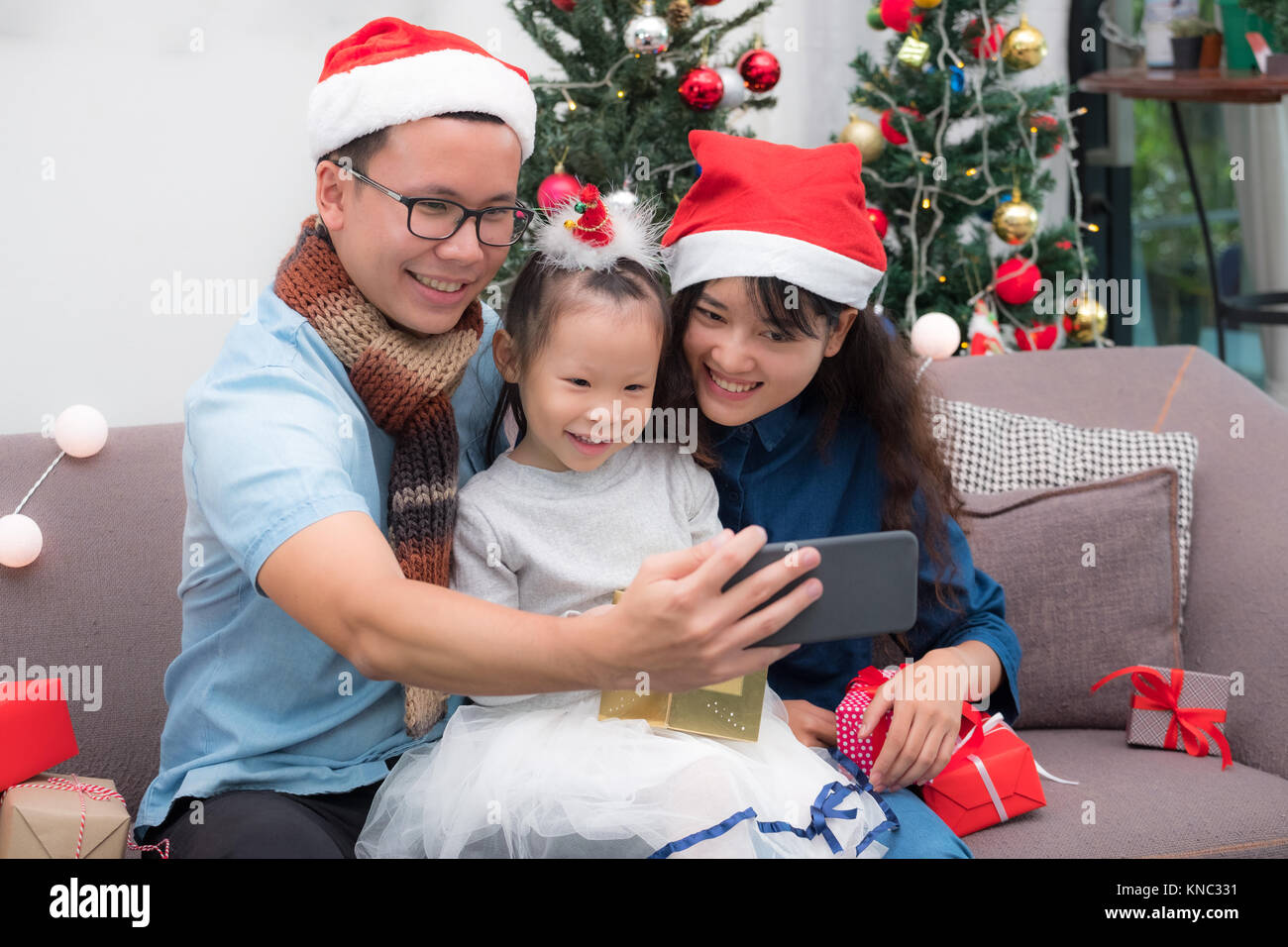 Happy family Asia selfie with mobile at sofa,father and mother wear santa claus hat give Christmas gift box to child - Stock Image