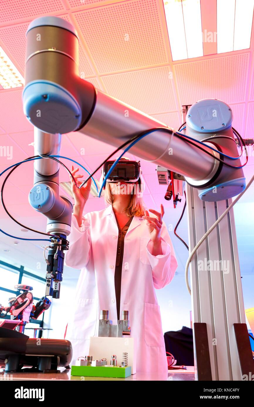 Robotic arm with artificial vision, Researcher with virtual reality glasses, VR, Humanoid robot for automotive assembly - Stock Image