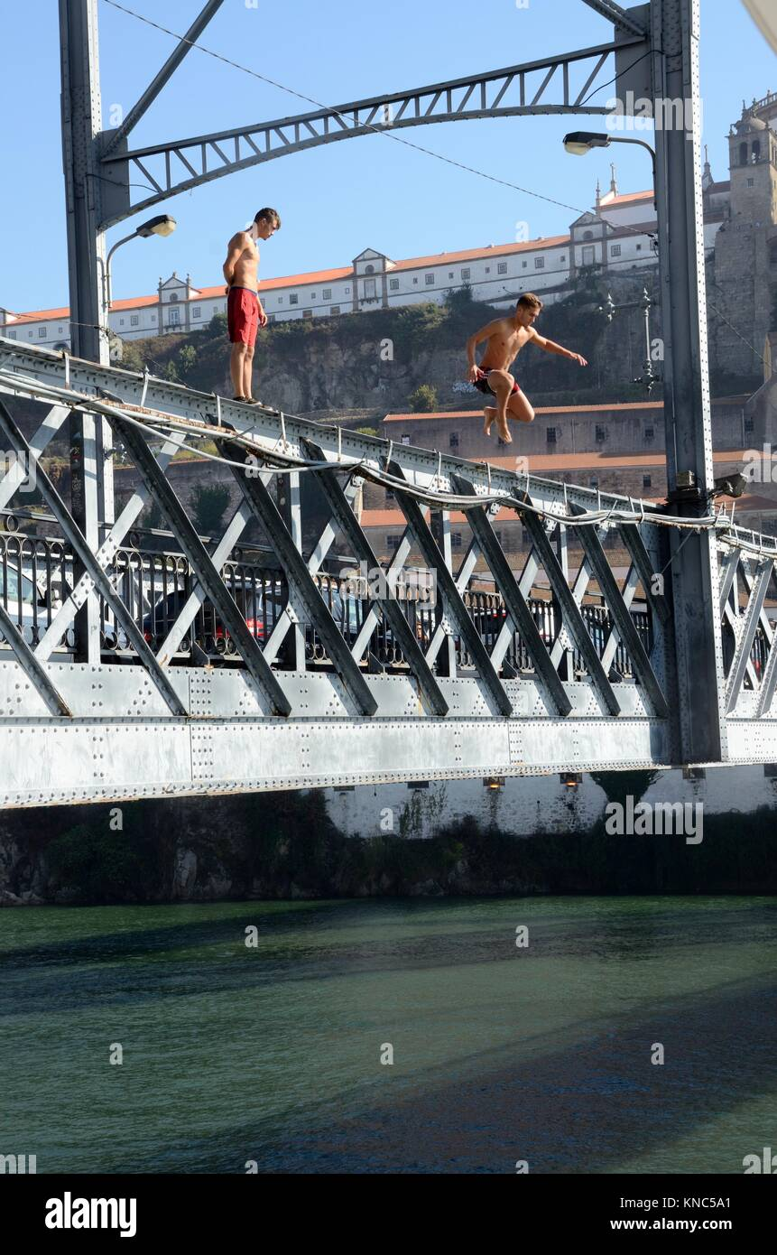 Young men jumping of Luis ! Bridge to entertain tourists for money Porto Portugal - Stock Image
