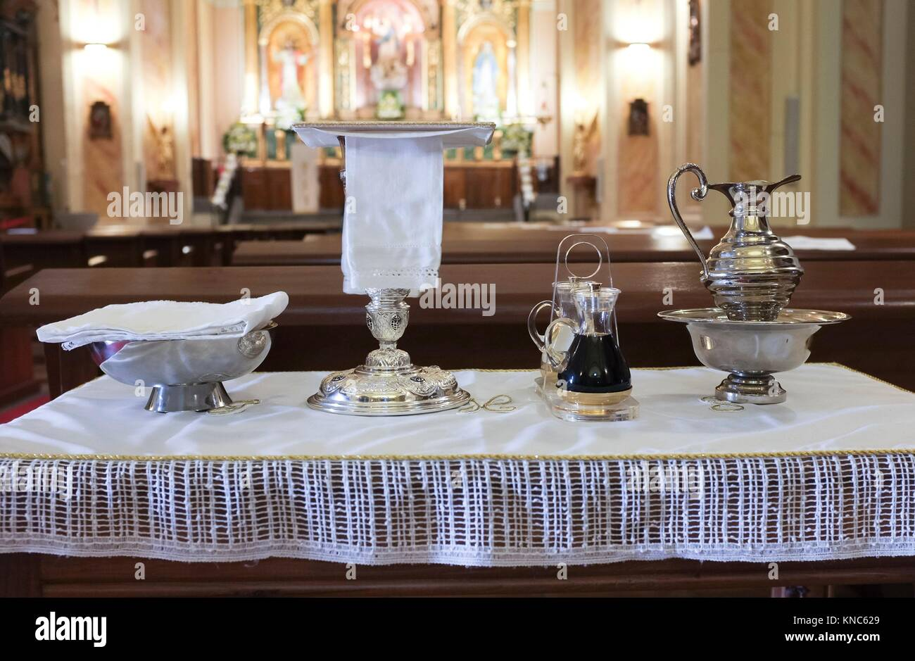 Catholic liturgical objects displayed over table at church. Chalice, communion wafers, wine, water, ewer and basin. Stock Photo