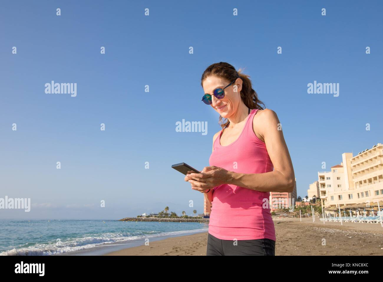 woman with pink sleeveless t-shirt smiling and touching mobile phone smartphone at beach with sea and buildings - Stock Image