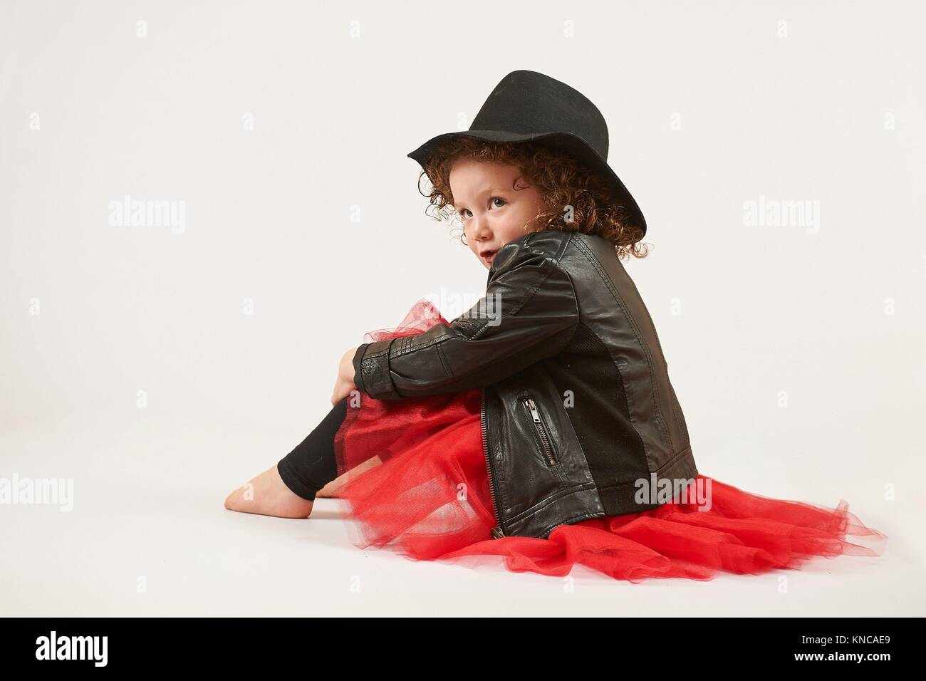 04e4a8206e275 Little girl with black hat sitting and pouting. side view. - Stock Image