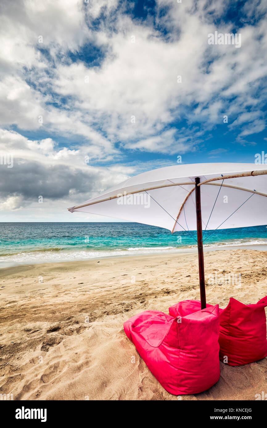 Bean bag chairs and umbrella for rent on White Sand Beach (Pantai Bias Putih). Manggis subdistrict, Karangasem Regency, - Stock Image