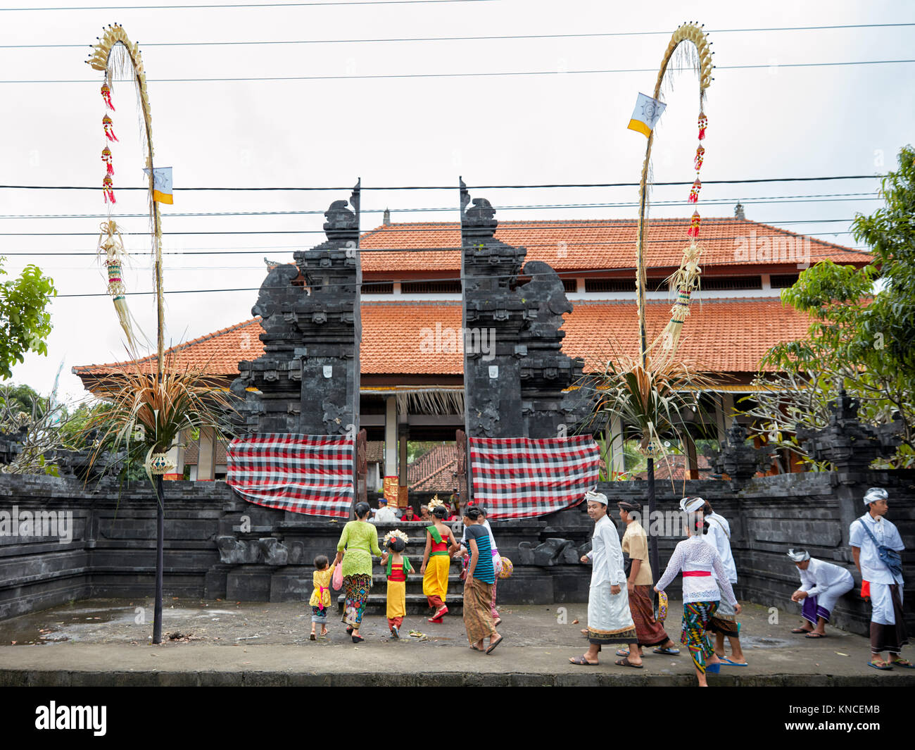 People wearing traditional Balinese clothing go to a local temple near Bugbug village. Karangasem Regency, Bali, - Stock Image