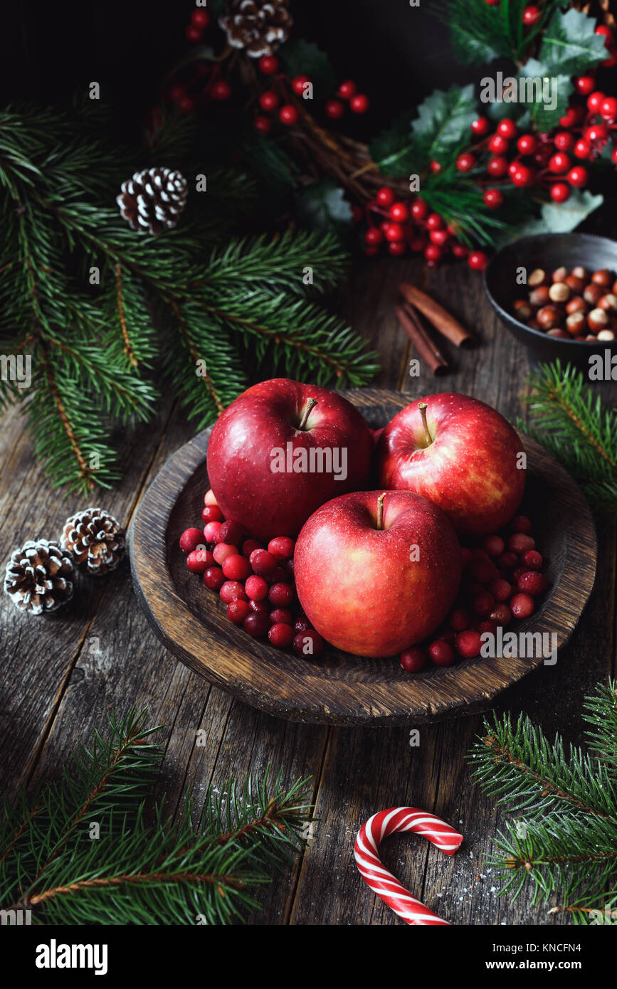 Red apples, cranberries and fir tree branches. Christmas still life. Winter wallpaper. Vertical composition - Stock Image