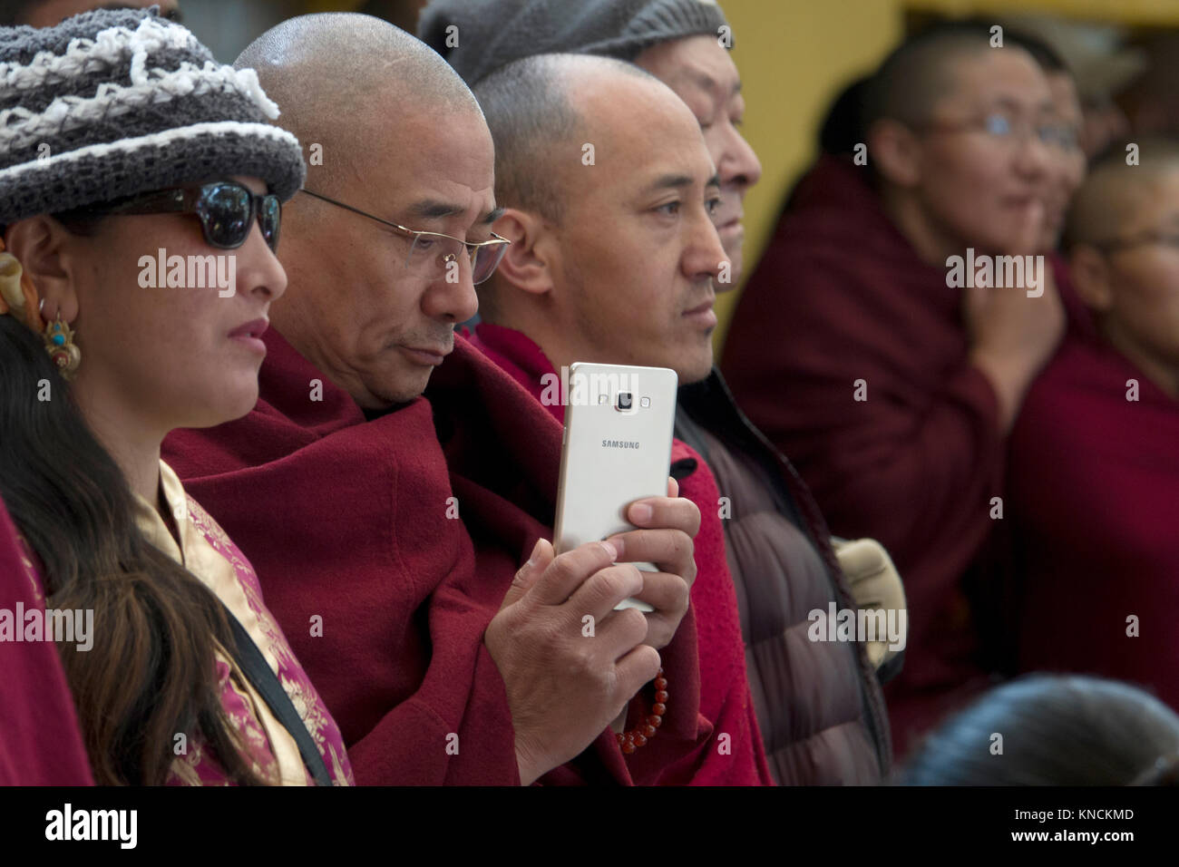 Tibetan monk uses Samsung smart phone to take a photo at Tsuglhakhang Complex in Mcleod Ganj - Stock Image