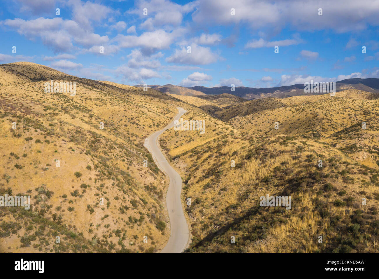 Drone photograph of asphalt road leading through the dry hills of southern California canyons. - Stock Image