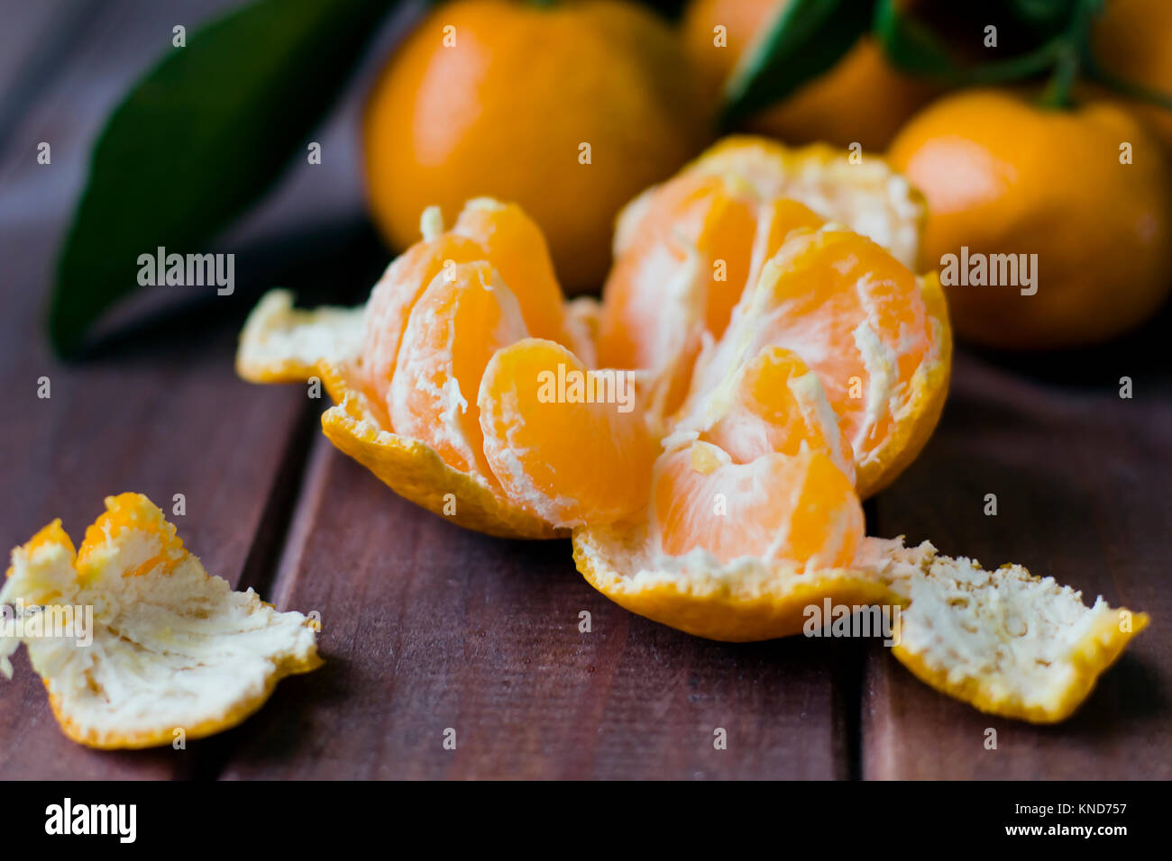 Fresh opened tangerine on wooden background - Stock Image