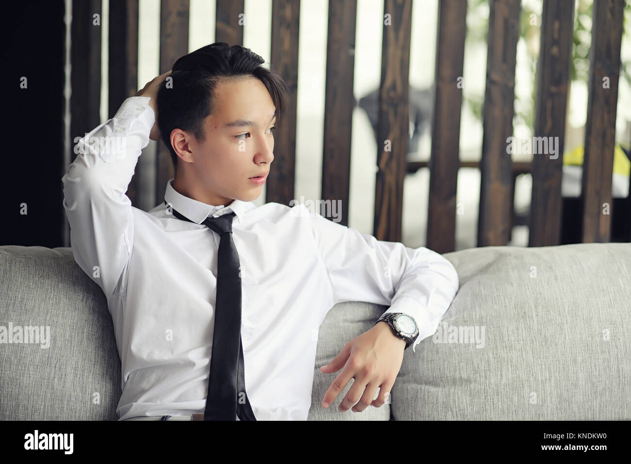 A young Asian businessman is waiting for a partner in a cafe. Bu - Stock Image