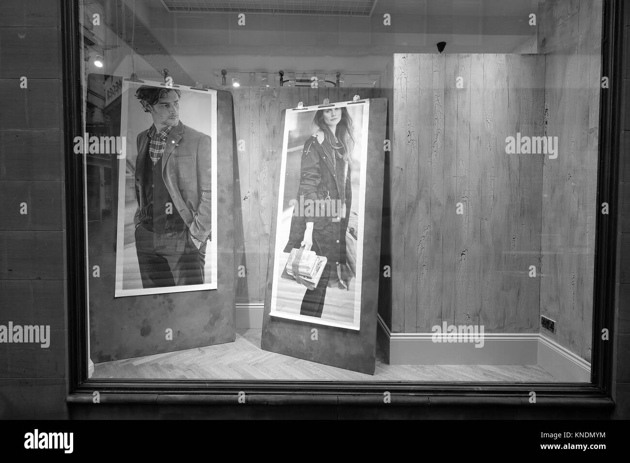 Shop window with two posters one of a man one of a woman looking at each other - Stock Image