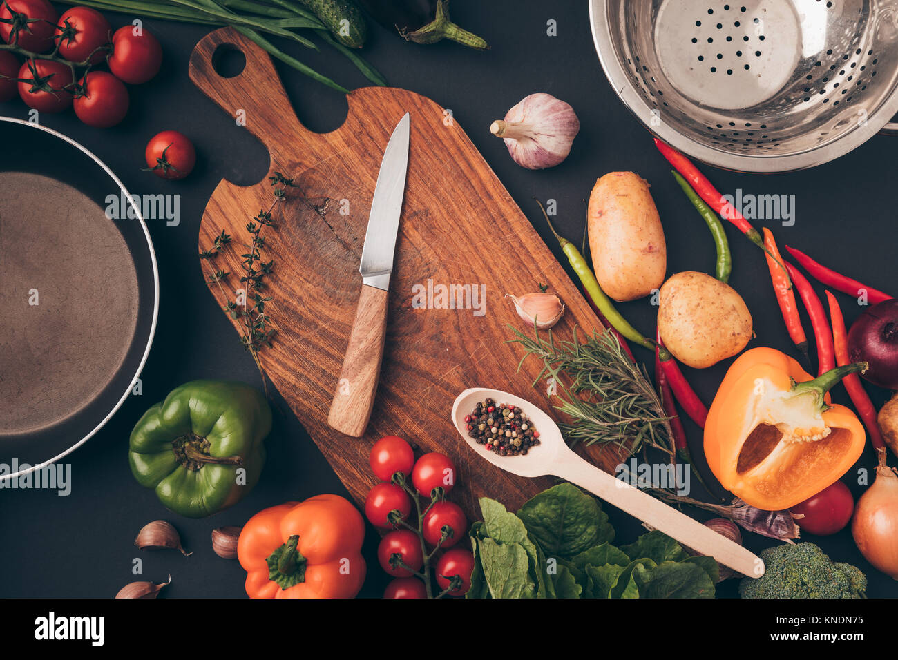 top view of knife and wooden board among vegetables - Stock Image